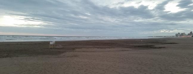 Atardecer con la playa desierta y la ciudad al fondo