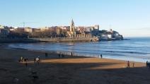 Invierno en la playa de San Lorenzo, con la iglesia de San Pedro y el Elogio al Horizonte al fondo