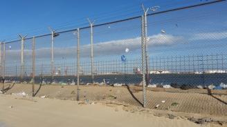 Valla hacia el puerto marroquí de Beni Ensar al final del Paseo Marítimo