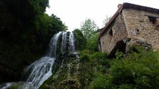 Detalle de la cascada cayendo justo al lado de una casa