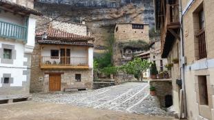 Centro de Orbaneja con casas al fondo encastradas en la roca
