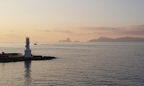 Faro de La Savina con Es Vedrà en el horizonte