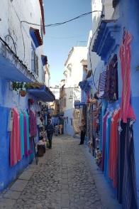 Colorida calle comercial de Chefchaouen, azul y blanca, con tejidos de vivos colores