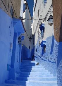 Escalinatas y bajos azules de una calle de Chefchaouen con casas encaladas en blanco
