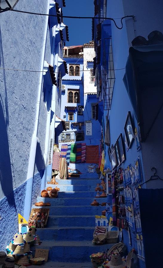 Escalinata azul entre paredes azules plagada de coloridas artesanías, Chefchaouen, Marruecos