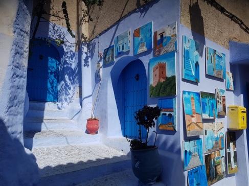 Venta de láminas azules sobre una pared azul en Chefchaouen, Marruecos