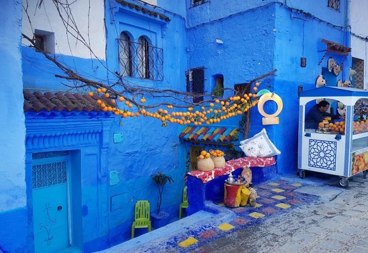 Venta de naranjas en una calle completamente azul de Chefchaouen, Marruecos