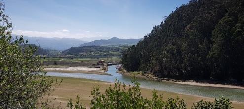 Ría de Tina Mayor y Caño del Mazo, con la Cofradía de Pescadores de Bustio y los Picos de Europa de fondo, desde la carretera de Pechón