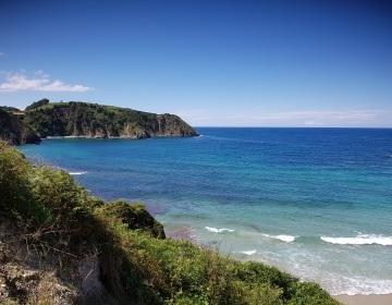 Ensenada de Pechón con pleamar, con el extremo de Amio en primer plano y el hueco hacia la playa de Aramal al fondo