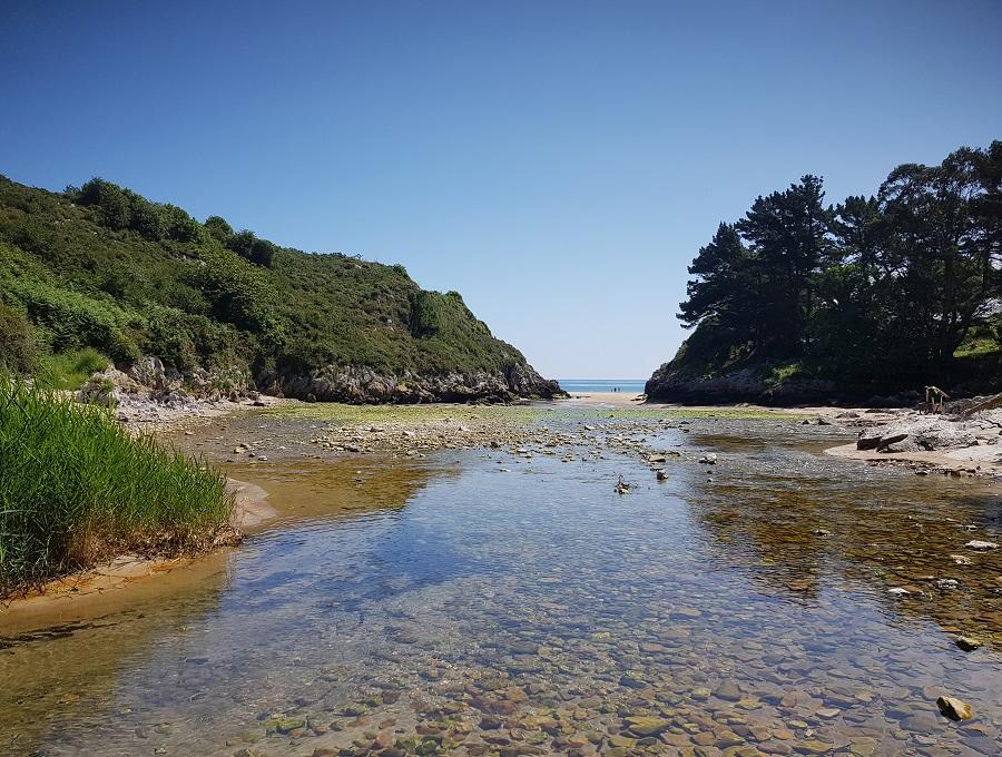Al fondo, la playa de La Huelga, desde la desembocadura del río San Cecilio, con bajamar