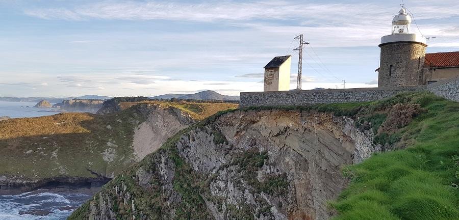 Linterna del cabo de Faro Vidio y, al fondo, los acantilados hacia el centro de Asturias