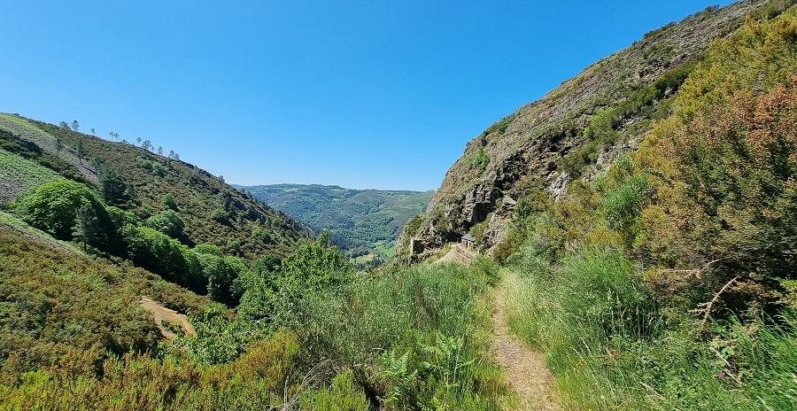 Último tramo de bajada a Mina Carmina, que ya se ve al fondo, con camino casi imperceptible por la vegetación